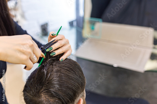 Female hairdresser hands doing haircut for male client using professional hairdresser tools scissors, brush on hairdresser work space. Hairdresser service. Beauty salon hair cut service. Close up