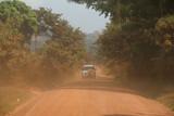 Fototapeta Sawanna - auto terenowe jadące po szutrwoej drodze wśród dziekij roślinności na afrykańskiej sawannie