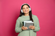 canvas print picture - Young woman listening to audiobook on pink background
