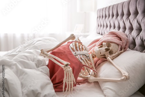 Human skeleton in silk pajamas and towel lying on bed indoors Canvas Print