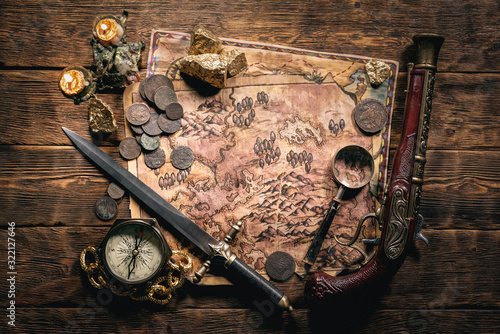 Fototapeta Pirate treasure map and other accessories on brown wooden table flat lay background. obraz