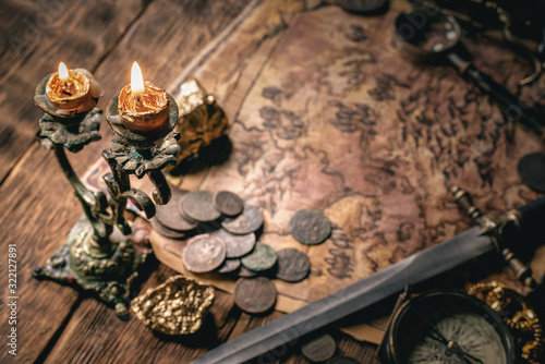 Fototapeta Pirate treasure map on brown wooden table closeup background.