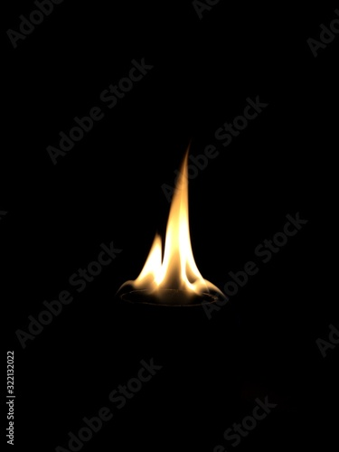 Vertical shot of a beautiful flame with a pitch-black background