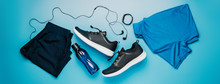 Flatlay Blue Clothing For Running Or Crossfit, Headphones, Fitness Bracelet, Water Bottle, Shorts And T-shirt On A Blue Background