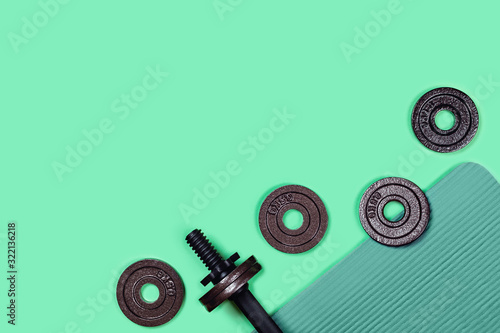 Fototapeta Sports picture. Dumbbells located on sports mat on mint green background. Flat lay, top view, copy space. obraz na płótnie