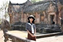 Portrait Of Young Cute Asian Woman In White Hat And Striped Shirt In Large Ancient Hindu Khmer Empire Temple. Prasat Hin Phanom Rung, Thailand