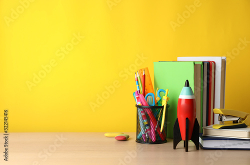 Fototapeta Bright toy rocket and school supplies on wooden table