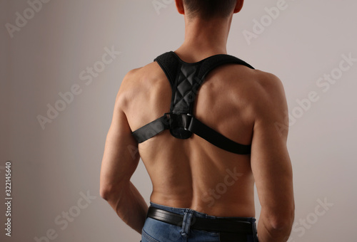 Foto Attractive muscular man with posture corrector