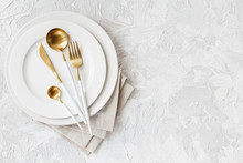 Beautiful Gold And White Cutlery On White Plate On Light White Gray Background