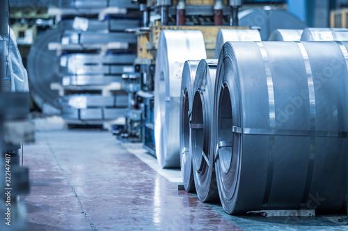 Fototapeta Industrial background. Big size steel coil stored inside industrial warehouse, blue toned image . obraz