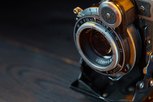 Old Vintage Camera On The Wooden Table. Cinematic Style.