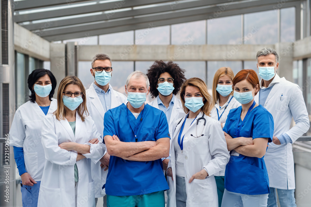 Fototapeta Group of doctors with face masks looking at camera, corona virus concept.