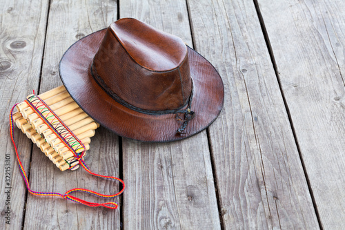 Photo Multiple pipes pan flute and leather cowboy hat lying on square-edged flooring,