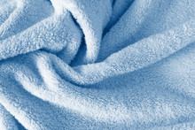 Fluffy Classic Blue Towel Background, Close-up. Gentle Baby Pastel Fabric With Waves And Folds. Folded Tender Light Blue Towel Texture. Bath Fluffy Towel, Spa Background