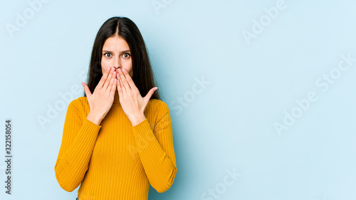 Young caucasian woman isolated on blue background shocked, covering mouth with hands, anxious to discover something new Canvas Print