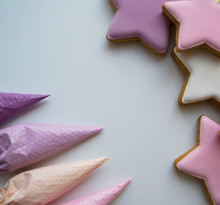 Pink, White, Purple Stars Next To Pastry Bags Filled With Icing