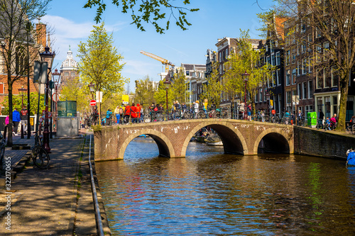 Fototapety, obrazy: Stunning view of Amsterdam canals and typical dutch houses with narrow cosy streets filled with bicycles in the capital of Netherlands, Europe on a beautiful sunny day.