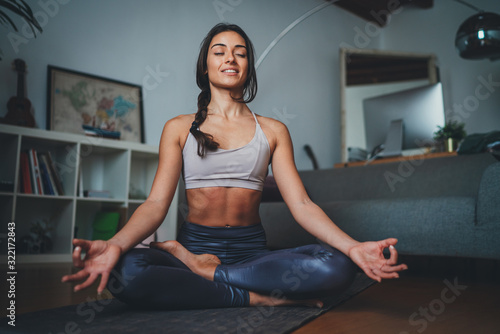 Slika na platnu Young beautiful woman meditating at modern home interior sitting on yoga mat and