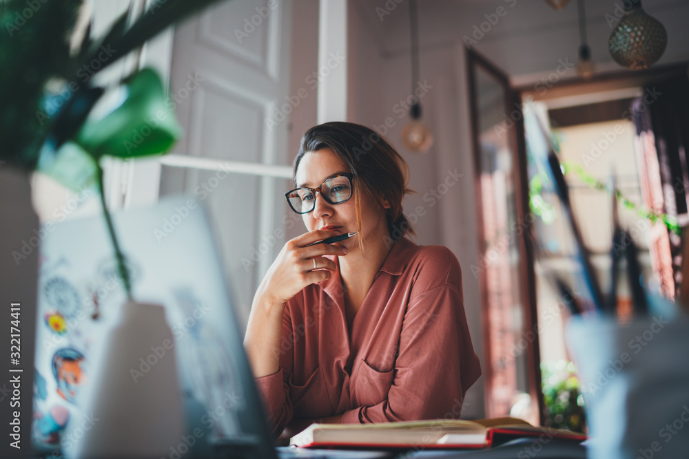 Fototapeta Young businesswoman thinking about something while sitting front open portable laptop computer reading email from client, long hours of work concept