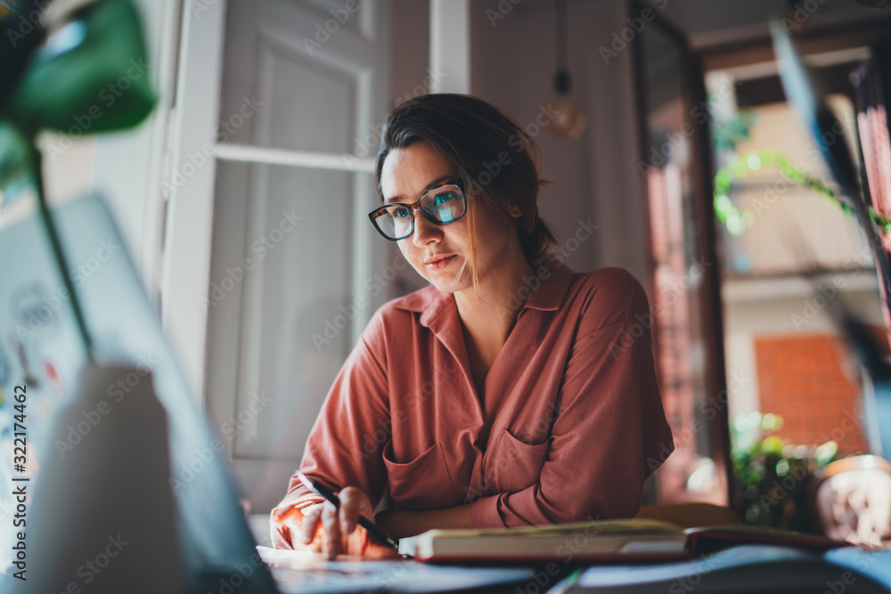 Fototapeta Pretty young woman an advertising copywriter in eyeglasses working at home using laptop, female graphic designer working in modern studio, Networking Freelancer Businesswoman Designer Entrepreneur