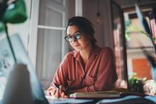 Pretty Young Woman An Advertising Copywriter In Eyeglasses Working At Home Using Laptop, Female Graphic Designer Working In Modern Studio, Networking Freelancer Businesswoman Designer Entrepreneur