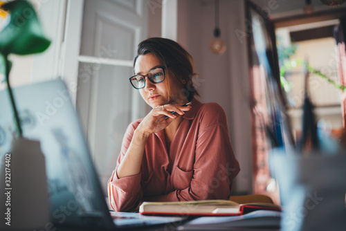 Beautiful businesswoman sitting at table opposite laptop in workplace brainstorming new project, People technology Concept