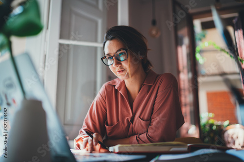 Pretty young woman an advertising copywriter in eyeglasses working at home using laptop, female graphic designer working in modern studio, Networking Freelancer Businesswoman Designer Entrepreneur