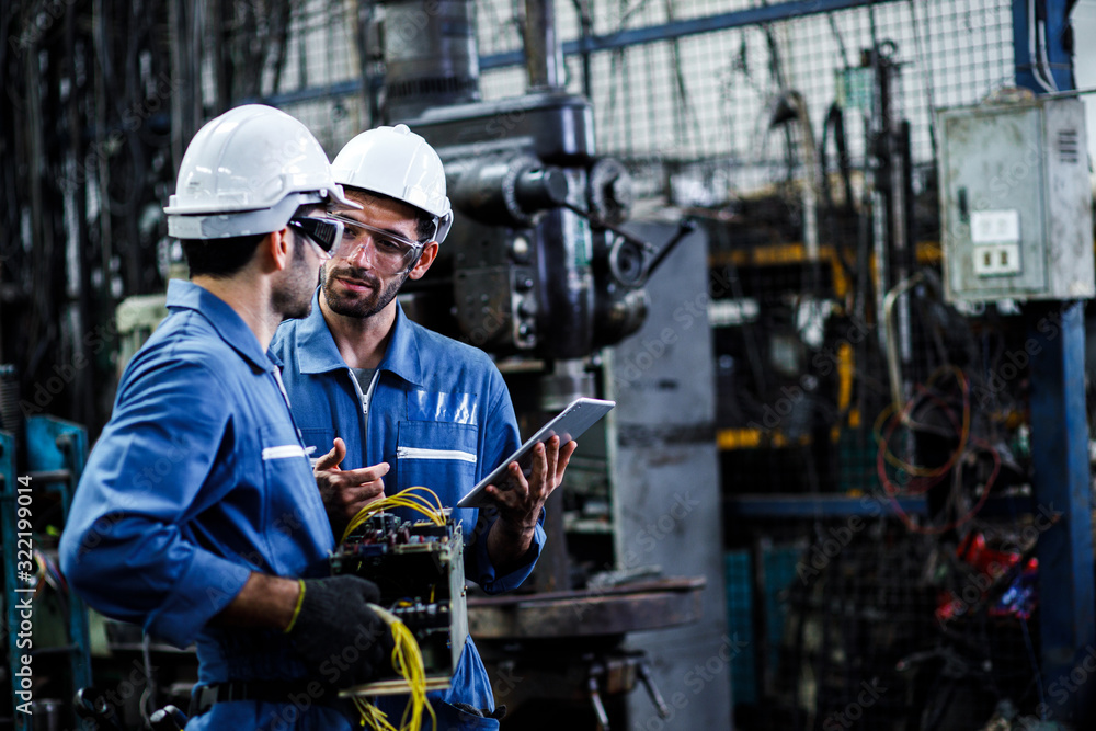 Fototapeta Two men engineer talking in modern factory. Production line machine and setting it for work.