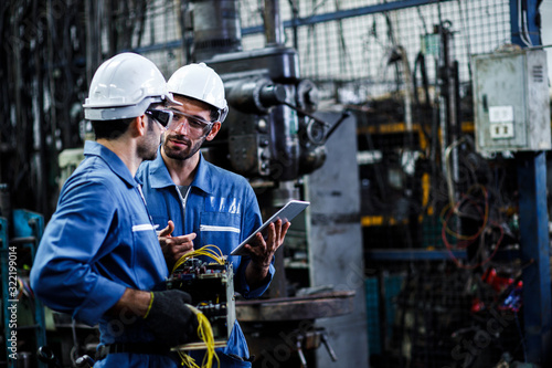 Obraz Two men engineer talking in modern factory. Production line machine and setting it for work. - fototapety do salonu