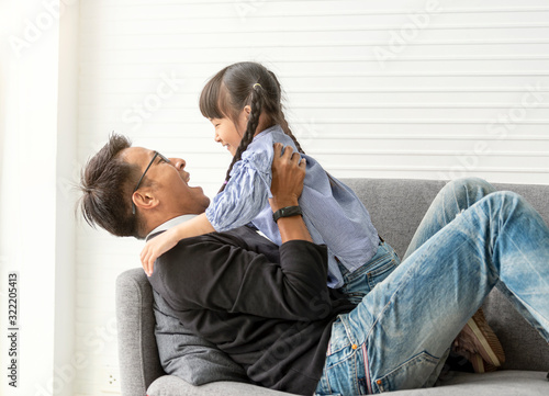 Obraz Asian father and daughter playing together in living room at home. - fototapety do salonu