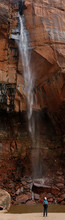 Observing A Waterfall That Is Super Tall Among Red Rocks.