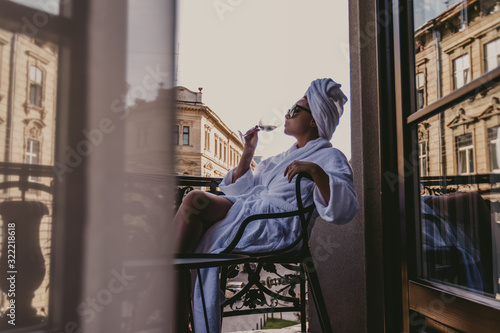 woman in bathrobe on the balcony while singing light wine Wallpaper Mural