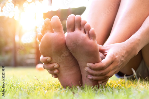 Foot Pain Leg of woman sitting on grass in the park holding he feet and stretch the muscles in morning sunlight Canvas