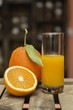 Closeup shot of a glass of orange juice and fresh oranges on a wooden crate with blurry background