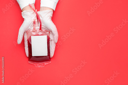 Fotografía Hands of doctor with blood pack for transfusion on color background