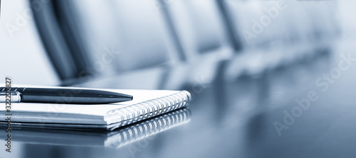 Obraz Notepad on a table with pen before meeting, blue tone, business concept with copy space - fototapety do salonu