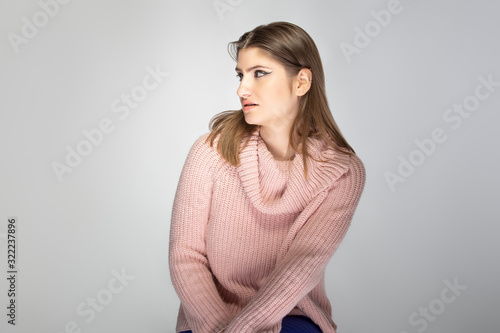 Close up portrait of a young Caucasian woman wearing a pink sweater on a grey background Billede på lærred