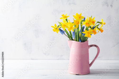 Beautiful spring composition with daffodil flowers in vase on white background Tableau sur Toile