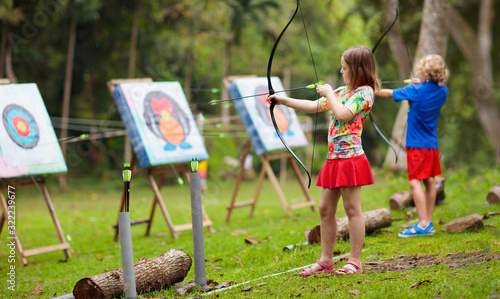 Photo Archery for child. Kids shoot a bow. Arrow, target