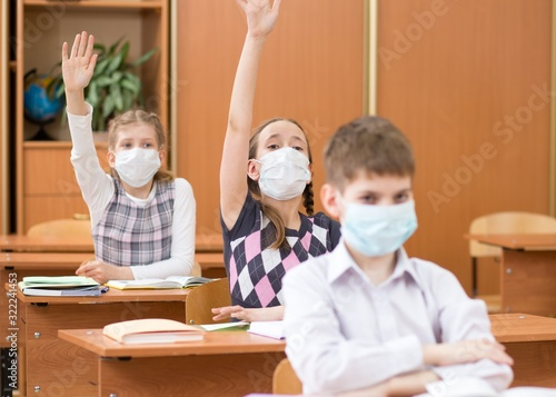 Fotomural Schoolers students wearing protection mask to prevent virus on lesson in classro