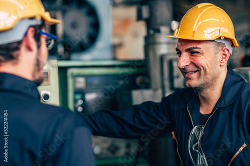 Obraz happy worker, smiling industrial technician engineer enjoy working together with coworker. - fototapety do salonu