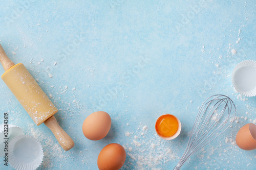 Obraz na plátně Baking background with rolling pin, whisk, eggs, flour on blue table top view
