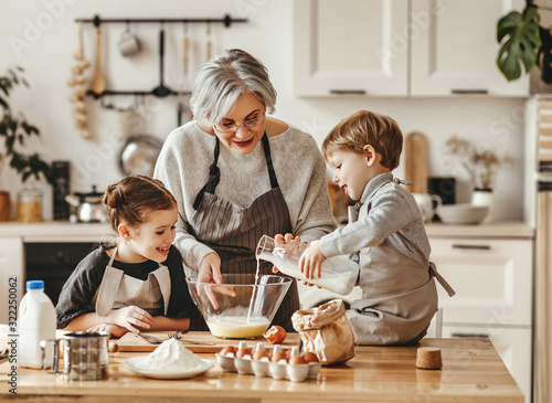 Fototapeta happy family grandmother and grandchildren cook in the kitchen, knead dough, bake cookies. obraz