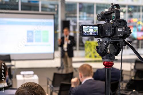 Obraz Still camera recording male speaker in conference hall - fototapety do salonu