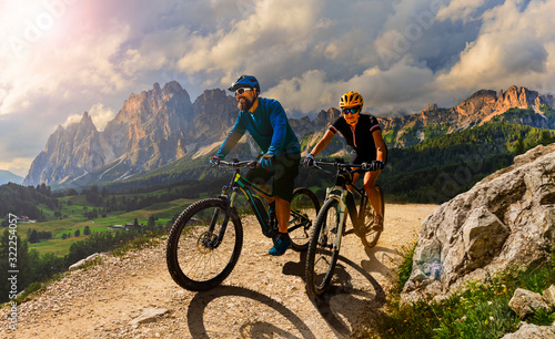 Cycling woman and man riding on bikes in Dolomites mountains andscape. Couple cycling MTB enduro trail track. Outdoor sport activity. #322254057