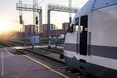 White and grey passenger train sitting on track ready to go in modern railway central station, Turku, Finland Fototapeta