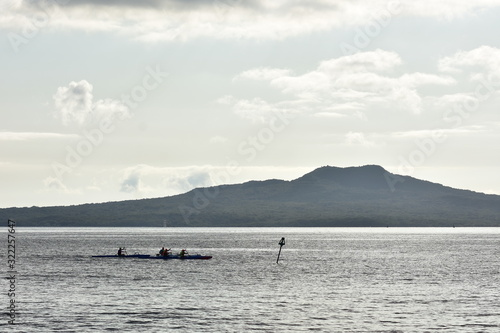 Crews paddling hard on board waka ama in calm channel in front of island with volcanic cone Wallpaper Mural