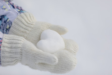 Valentine day background. Female hands in knitted mittens with heart of snow in winter day. Love concept.