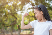 Photo Happy Little Asian Girl Child Standing With Big Smile. Girl With Green Apple Showing Biceps..fresh Healthy Green Bio Background With Abstract Blurred Foliage And Bright Summer Sunlight