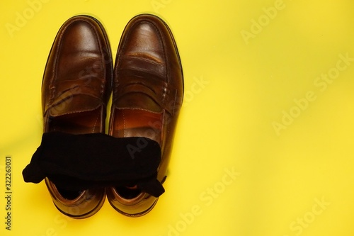 High angle shot of brown leather shoes with a yellow background